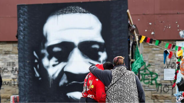Una pareja frente a un retrato de George Floyd este 20 de abril de 2021 en Minéapolis, mientras Estados Unidos estaba a la espera del veredicto del juicio contra Derek Chauvin, el expolicía acusado de matar a Floyd en mayo pasado. (EFE)