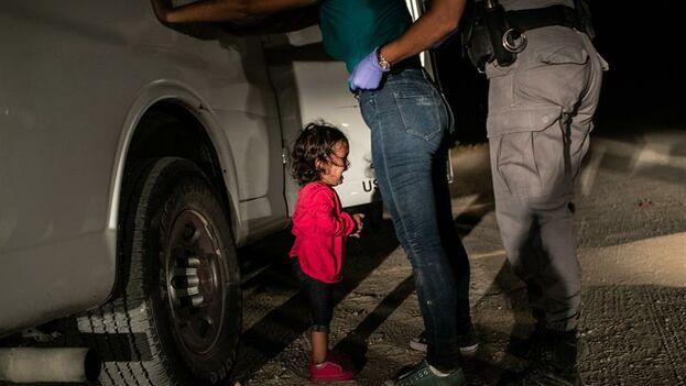 Fotografía tomada por John Moore el 12 de junio de 2018, y cedida por la organización World Press Photo (WPP), que muestra a una solicitante de asilo hondureña de dos años que llora mientras su madre es registrada y detenida cerca de la frontera con México, en McAllen, en Texas. (EFE/John Moore/Getty Images)