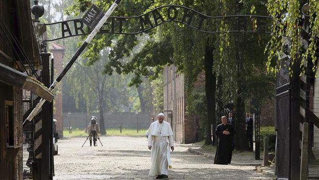 Franciso camina cabizbajo al pasar la puerta 'Arbeit macht Frei' de entrada al campo de exterminio. (EFE/Pawel Supernak)