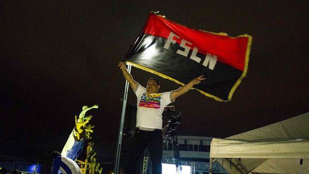 Un hombre sostiene una bandera del partido en el Gobierno (FSLN) durante la celebración de los resultados en las elecciones municipales. (EFE)