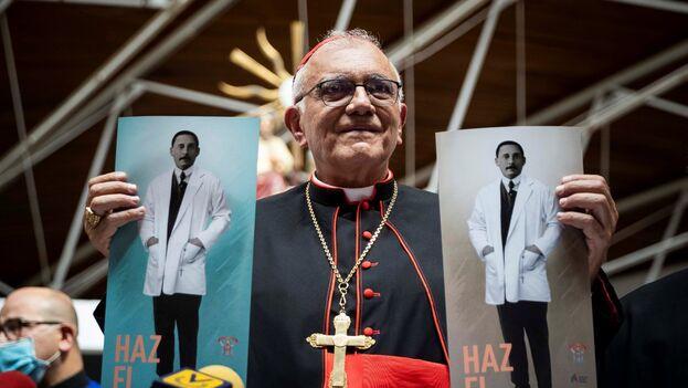 El cardenal Baltazar Porras sostiene afiches de José Gregorio Hernández en la Iglesia Parroquia Inmaculado Corazón de María de Caracas. (EFE)