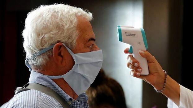 Grupos de personas pasan controles de salud este domingo, en el aeropuerto Internacional José Martí de La Habana. (EFE)