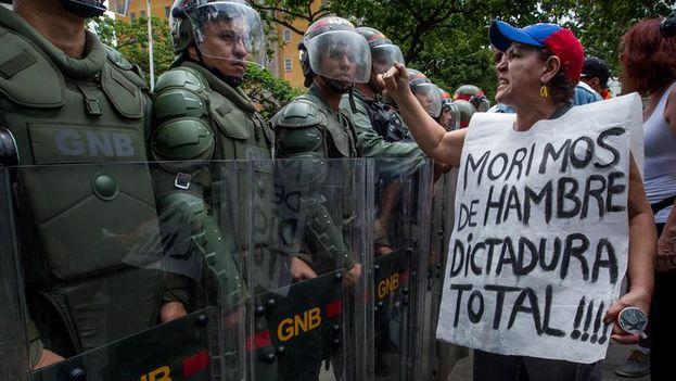 Una mujer protesta frente a miembros de la Guardia Nacional Bolivariana en la marcha del miércoles en Caracas. (EFE/Miguel Gutiérrez)