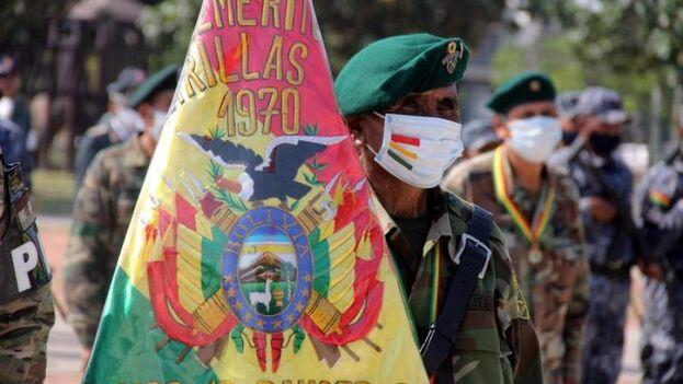 Un excombatiente con una bandera participa en un homenaje a militares que capturaron al Che Guevara, este viernes en Santa Cruz, Bolivia. (EFE/Juan Carlos Torrejón)