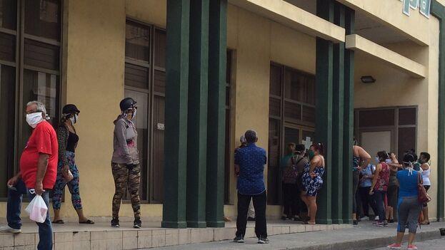 Habitantes de Santa Clara hacen fila en el Banco Popular para depositar dinero en las tarjetas y poder adquirir bienes mediante la plataforma digital tuenvío.cu. (Laura Rodríguez Fuentes)