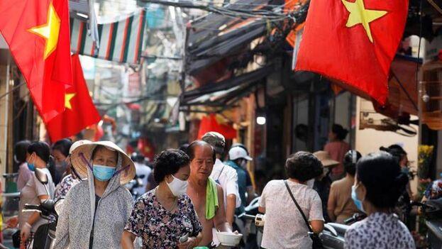La gente camina bajo banderas nacionales vietnamitas en un callejón en Hanoi, Vietnam. (EFE/EPA/Luong Thai Linh/Archivo)