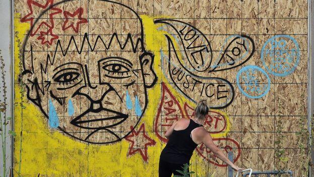 Un manifestante pintando un mural durante una protesta por el tiroteo al afroamericano Jacob Blake por parte de agentes de Policía, en Kenosha. EFE)