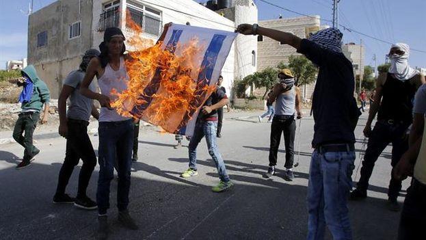 Jóvenes palestinos queman una bandera de Israel (Foto EFE/Abed Al Hashlamoun)
