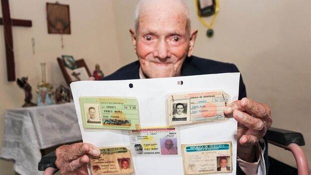 Juan Vicente Pérez Mora, de 111 años de edad, muestra sus distintas cédulas de identidad. (EFE)