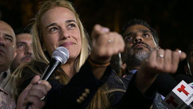 Lilian Tintori con las manos simulando ser esposada en un gesto simbólico minutos después de conocerse la sentencia para su esposo, Leopoldo López. (EFE/Fabiola Ferrero)