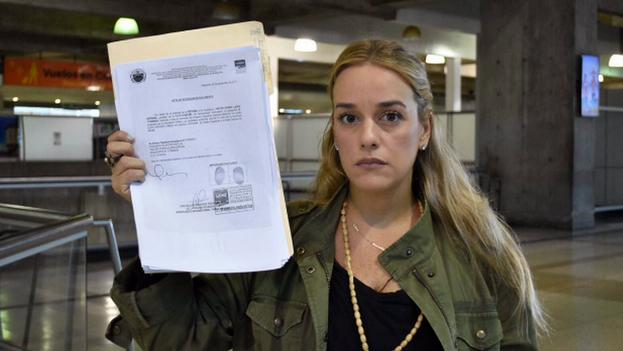 Lilian Tintori, activista política y esposa del dirigente opositor venezolano privado de libertad Leopoldo López, muestra el documento que justifica la prohibición de salida de Venezuela. (Twitter: @liliantintori)