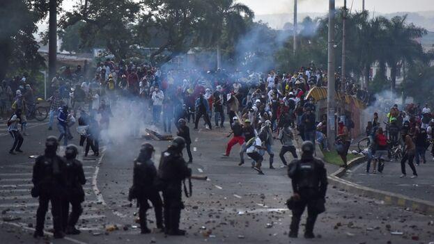 Manifestantes se enfrentan a policías durante una jornada de protestas en contra de la reforma tributaria, el 29 de marzo de 2021, en Cali (Colombia). (EFE/Ernesto Guzmán Jr.)
