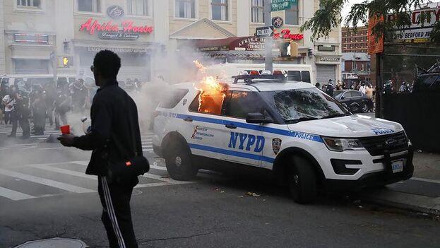 """Manifestantes de """"Black Lives Matter"""" incendian un carro del Departamento de Policía de la ciudad de Nueva York durante las manifestaciones por la muerte de George Floyd. (EFE/EPA/Kevin Hagen)."""