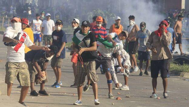 Manifestantes enfrentan a la policía durante la huelga nacional convocada por sectores ciudadanos contrarios a la reelección de Morales. (Juan Carlos Torrejón/EFE)