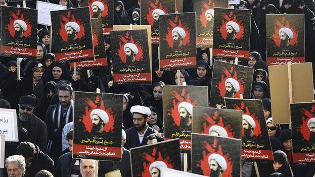 Manifestantes iraníes muestran carteles con el retrato del clérigo y dirigente chií, Nimr Baqir al Nimr, durante una protesta convocada en Teherán. (EFE/Abedin Taherkenareh)