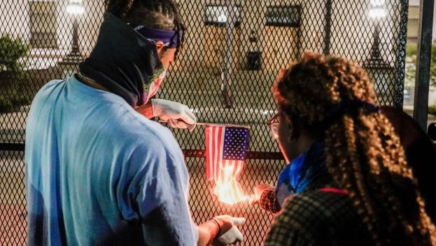 Manifestantes queman una bandera de Estados Unidos durante la tercera noche de protestas en Kenosha, Wisconsin. (EFE/EPA/Tannen Maury)