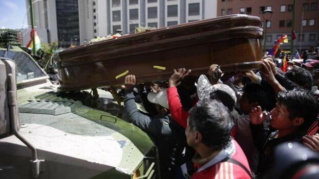 Manifestantes colocan un féretro sobre un vehículo militar en La Paz. (EFE)