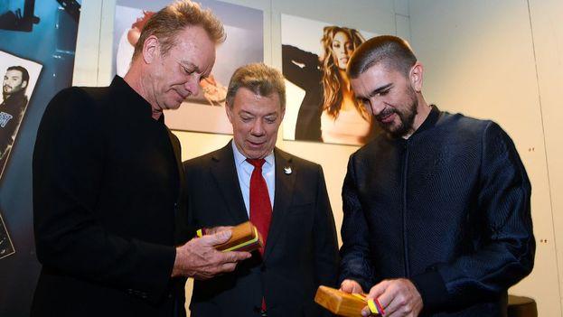 Juan Manuel Santos entrega a los músicos Sting y Juanes un regalo en la presentación del concierto por el Nobel de la Paz. (Twitter)