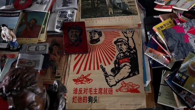 """Un póster que reza """"Quien se oponga al presidente Mao será aplastado"""" puesto a la venta junto a otros objetos de la época de Mao Zedong en el mercado Panjiayuan en Pekín (China).  (EFE/Rolex Dela Pena)"""