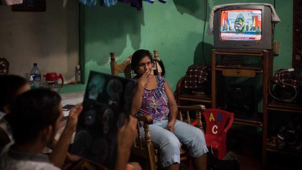 Juan Bosco Rivas Martínez se recupera del impacto de bala en su casa de habitación en Masaya. Mientras mira su radiografía con su madre al fondo. Carlos Herrera | Confidencial.