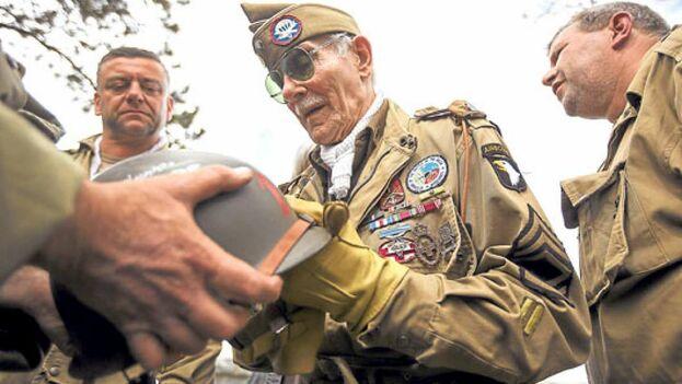 El veterano belga de la Segunda Guerra Mundial, George Michels, quien se unió a la fuerza de EE UU, firma autógrafos en Normandía. (EFE)