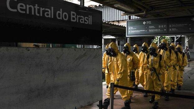 Miembros del ejército brasileño realizan limpieza y desinfección de los trenes, para evitar contagios por coronavirus este jueves en la Central de Brasil, en Río de Janeiro (EFE/ Antonio Lacerda)