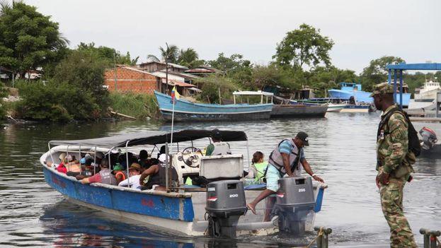 Migrantes saliendo en lanchas hacia Capurganá en el muelle El Waffe, en Colombia. (El País)