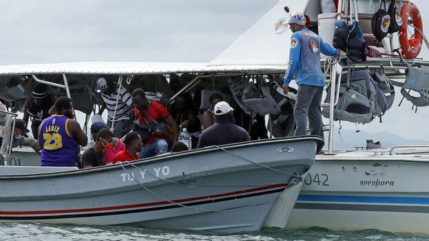 Migrantes haitianos viajan con sus pertenencias hacia un campamento donde pasarán la noche para iniciar su viaje hacia el tapón del Darién, el 27 de septiembre de 2021, en Acandi (Colombia). (EFE/Mauricio Dueñas Castañeda)
