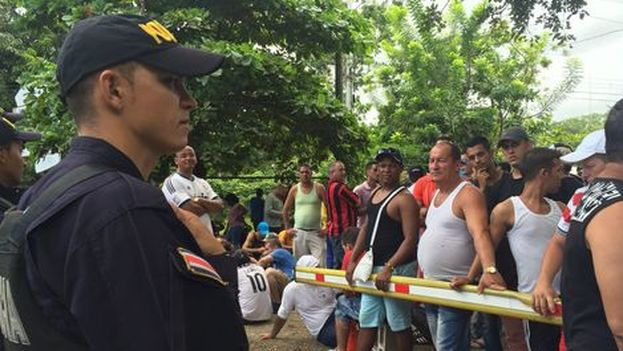 Migrantes cubanos en la frontera entre Costa Rica y Nicaragua ante la vigilancia de policías costarricenses. (Natasha Cambronero/La Nación)