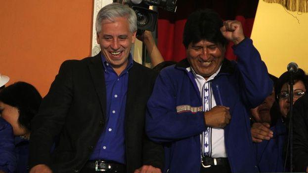 Evo Morales y su vicepresidente, Álvaro García Linera, saludan desde el Palacio de Gobierno tras conocerse su victoria electoral. (EFE/Martin Alipaz)