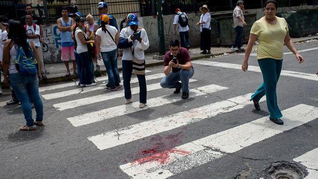 Vista de la mancha de sangre del joven de 17 años que resultó herido durante una concentración de la oposición este miércoles en Caracas. (EFE)