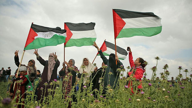 Mujeres palestinas con la bandera de ese estado en señal de protesta. (EFE)
