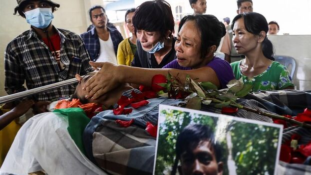 La madre del joven de 27 años Myo Ko Oo llora la muerte de su hijo fallecido en las protestas contra el régimen golpista durante su entierro en Rangún este martes. (EFE)