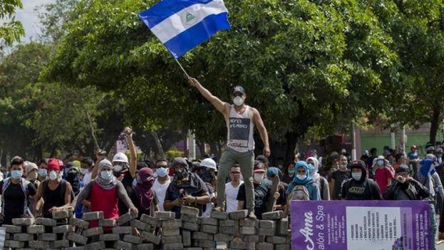 Un joven levanta una bandera de Nicaragua sobre una barricada de adoquines en Managua. (EFE)