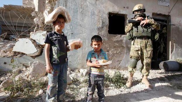 Niños sirios posan con alimentos y ayuda humanitaria entregada por soldados rusos. (EFE)