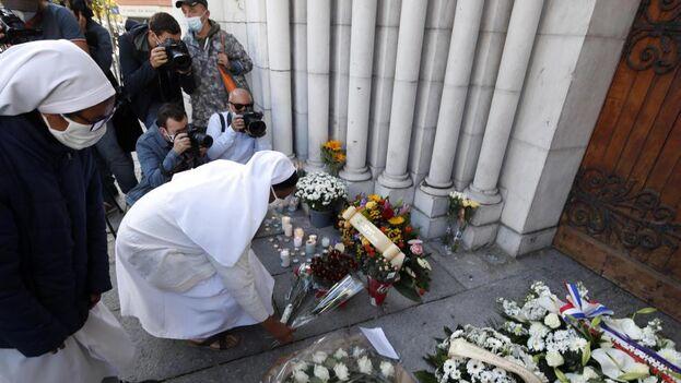 Una religiosa coloca un ramo de flores en la entrada de la iglesia de Notre Dame, en Niza, donde ocurrió el último atentado islamista. (EFE/Sebastien Nogier)
