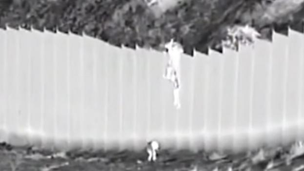 En el video hecho público por la Oficina de Aduanas se observa cómo un individuo deja caer a las dos niñas, de 3 y 5 años, desde lo alto del muro, que mide más de cuatro metros. (Captura)
