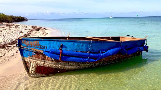 """Los migrantes viajaban en una precaria embarcación de color azul en la que se lee la frase: """"Dios está con nosotros"""". (Oficina de Aduanas y Protección Fronteriza de los EE UU)"""