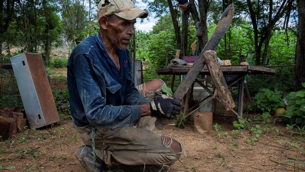 Orlando Gamero corta leña para cocinar dentro de la carcasa de una lavadora, usada a modo de estufa (EFE/Rayner Peña)