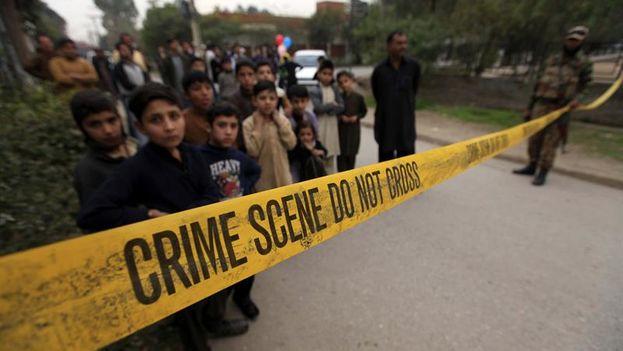 Varios niños observan el trabajo de los servicios de emergencia en lugar del atentado en Peshawar, Pakistán, ocurrido el 15 de febrero.