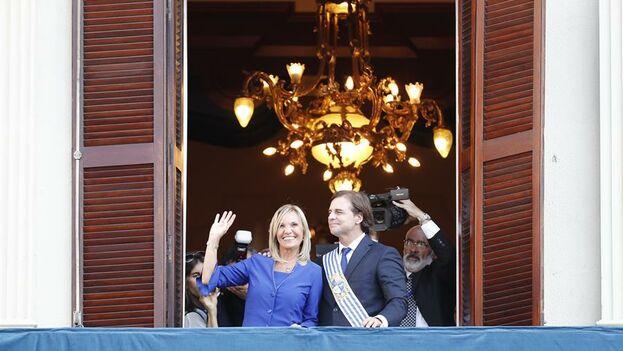 El presidente de Uruguay, Luis Lacalle Pou, y la vicepresidenta Beatriz Argimón, saludan a asistentes desde el balcón del Palacio Artigas. (EFE/ Sebastiao Moreira)