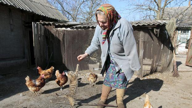 María Semenyuk jugaba con un gato cerca de su casa en el pueblo desierto de Patryshev, a 25 km de la central nuclear de Chernóbil, Ucrania, en 2011. Más de 330 residentes se negaron a ser reubicados después del accidente nuclear de 1986 y se quedaron a vivir dentro de la zona de exclusión de 30 kilómetros alrededor de la planta contaminada. (EPA / SERGUÉI Dolzhenko)