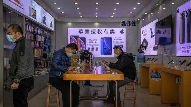 Personas con máscaras protectoras se sientan en una tienda de telefonía móvil en Wuhan, China, el epicentro del brote del coronavirus. (EFE)
