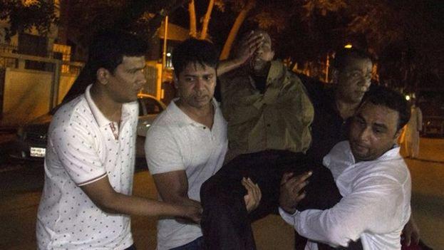 Personas transportan a un herido en el atentado de Bangladesh. (AFP)