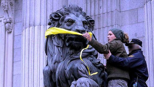 Policía detiene a un activista que coloca una mordaza a uno de los leones que flanquean el Congreso de los Diputados español como protesta. (Youtube)