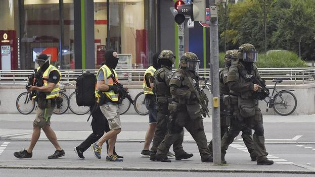 Policías de las Fuerzas Especiales se aproximan a lugar del tiroteo registrado en un centro comercial en Múnich este viernes. (EFE)