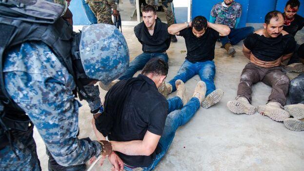 Policías custodian a un grupo de sospechosos de haber participado en el asesinato del presidente haitiano, Jovenel Moïse, en Puerto Príncipe. (EFE/Jean Marc Hervé Abélard)