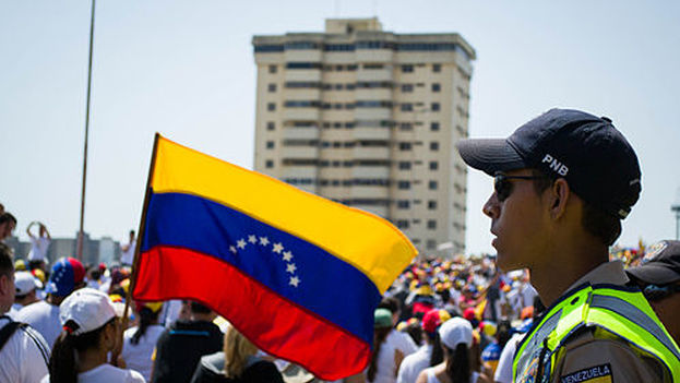Policías venezolanos de la Policía Nacional Bolivariana observando a manifestantes en Maracaibo. (Imagen de archivo)