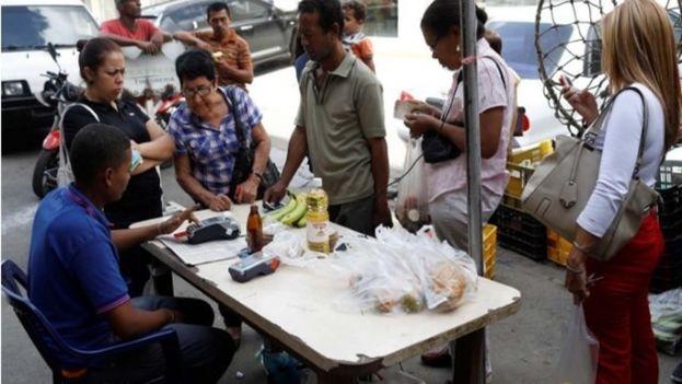 Productos de consumo diario como el café, la harina, la leche y el azúcar son ofrecidos ahora en bolsitas que pesan entre 50 y 150 gramos, cuyos precios suben cada día en los puestos ambulantes de los barrios populares. (EFE)