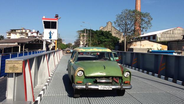 Un auto con la nueva matrícula circula por el Puente de Hierro sobre el Río Almendares en La Habana. (14ymedio)